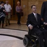 Brandon Coats leaves the courthouse at the end of the hearing with his attorney Michael Evans, right. The Colorado Supreme Court listens to arguments in the case of Brandon Coats, a quadriplegic medical marijuana patient who was fired from his job at Dish Network after testing positive for marijuana. Photograph by Kathryn Scott — Osler Denver Post via Getty Images